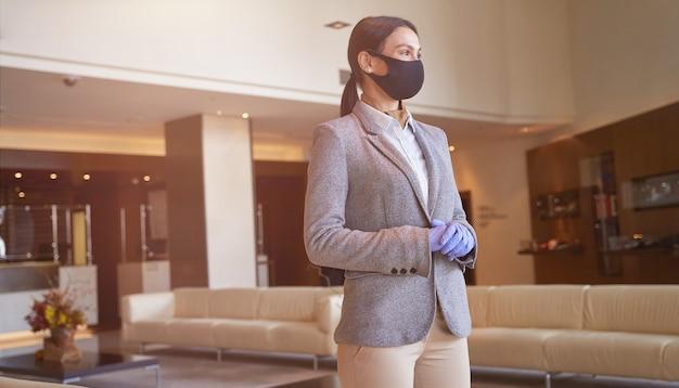 Mulher jovem calma de terno seguindo as regras sanitárias e usando máscara médica no corredor