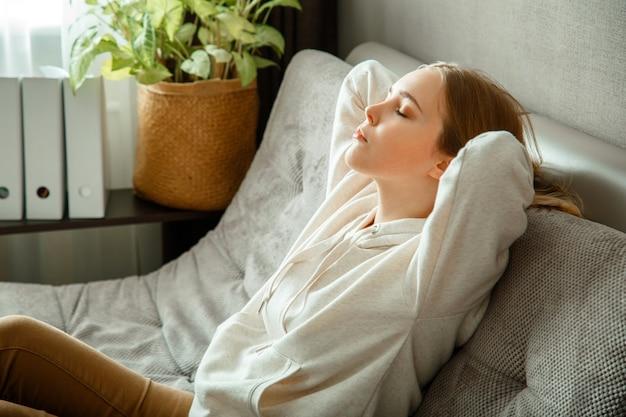 Mulher jovem calma feliz relaxe sentado no sofá confortável no interior de casa. menina adolescente descansando, bem-aventurança aproveite. retrato de mulher descansando com os olhos fechados.