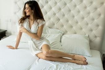 Mulher jovem, cama