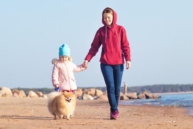Mulher jovem caminha com a menina e o cachorro na praia.