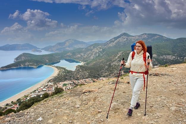 Mulher jovem caminha da maneira lícia com bastões de trekking.