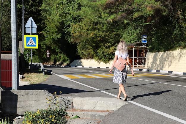 Mulher jovem caminha sozinha pela estrada deserta em direção à faixa de pedestres
