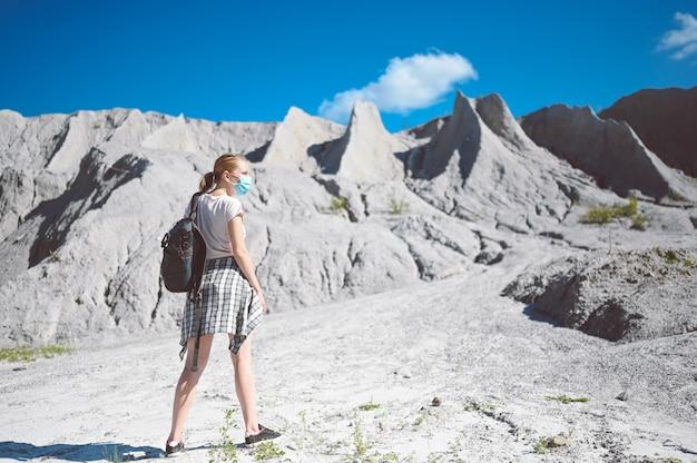 Mulher jovem caminhando contra as montanhas brancas usando máscara protetora facial para prevenção da covid 19.
