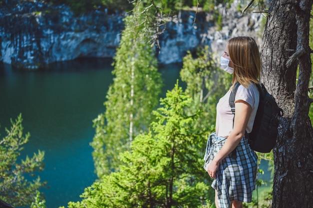 Mulher jovem caminhando contra o penhasco com árvores verdes e o lago azul da montanha usando máscara protetora facial para prevenção de covid 19.