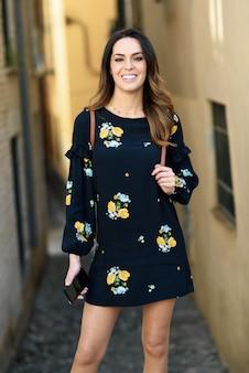 Mulher jovem caminhando em meio urbano. fêmea em roupas casuais, com cuidado de cabelo.