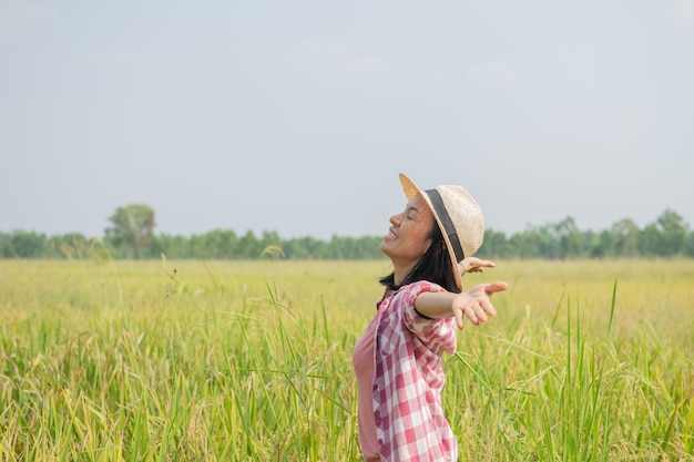 Mulher jovem caminhando em um campo de arroz na tailândia. viajar para lugares limpos da terra e descobrir as belezas da natureza. viajante jovem com chapéu em pé.