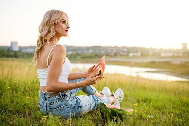Mulher jovem caminhando em um parque ao ar livre em um dia ensolarado, aproveitando o verão e sonhando