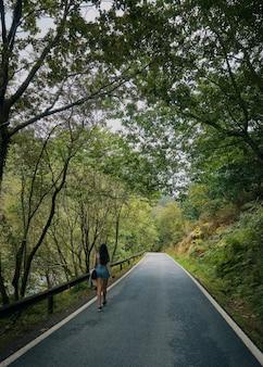 Mulher jovem caminhando em uma estrada rodeada por uma floresta no verão. galiza no verão. estrada de santiago