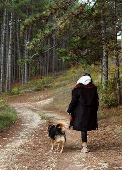 Mulher jovem caminhando em uma floresta com seu cachorro