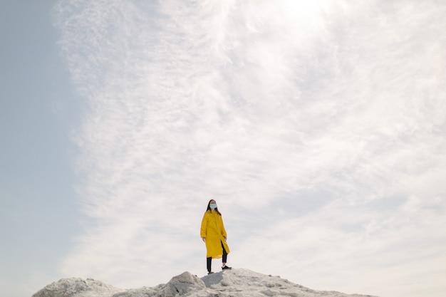 Mulher jovem caminhando em uma montanha de fosfato produzida por resíduos de fábricas de produtos químicos.