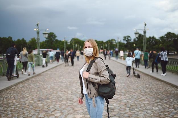 Mulher jovem caminhando em uma rua da cidade no meio da multidão com mochila e máscara protetora para prevenção de covid 19