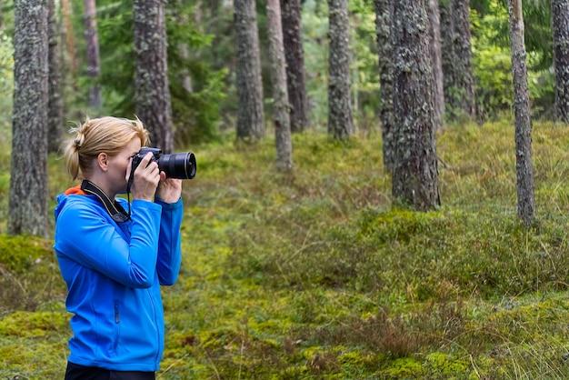 Mulher jovem, caminhando entre árvores e tirando fotos com a câmera. fotógrafo de mulher de meia-idade tirando foto na floresta de outono. fotografia da natureza.