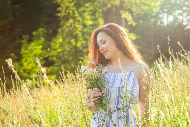 Mulher jovem caminhando entre flores silvestres no conceito de dia ensolarado de verão