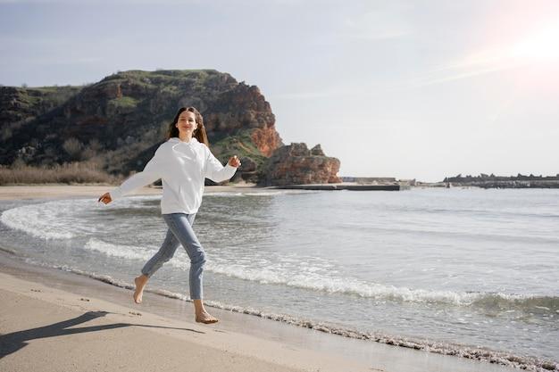 Mulher jovem caminhando na areia da praia