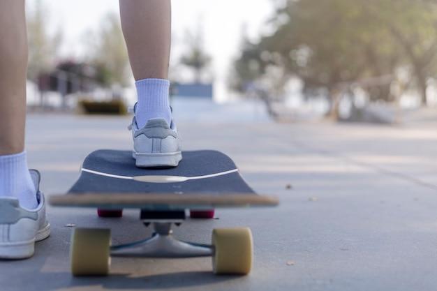 Mulher jovem caminhando na estrada secundária com o skate.