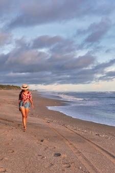 Mulher jovem caminhando na praia ao pôr do sol
