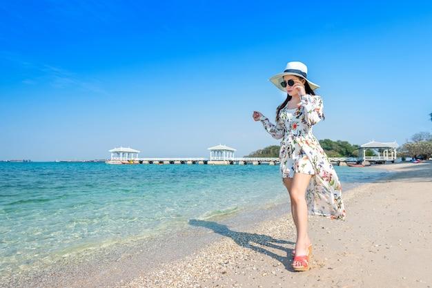 Mulher jovem caminhando na praia na ilha de si chang, tailândia.