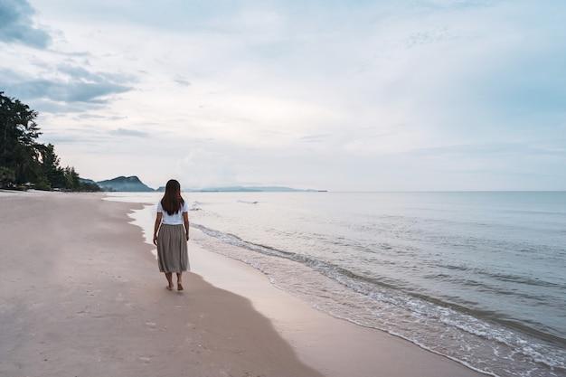 Mulher jovem caminhando na praia