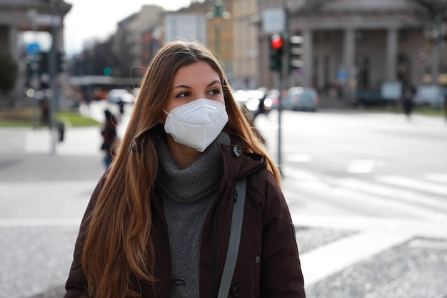 Mulher jovem caminhando na rua da cidade usando máscara protetora kn95 ffp2