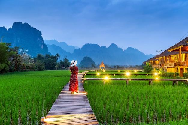 Mulher jovem caminhando no caminho de madeira com campo de arroz verde em vang vieng, laos.