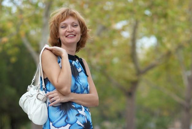 Mulher jovem caminhando no parque de outono