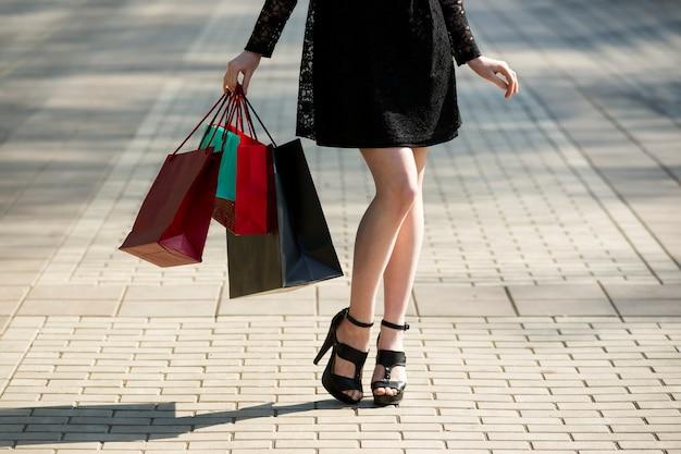 Mulher jovem caminhando pela cidade com sacolas de compras