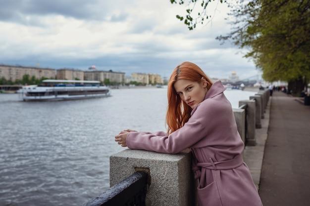 Mulher jovem caminhando pelas ruas de moscou. caminhando no calçadão. parque gorky no início da primavera ou outono