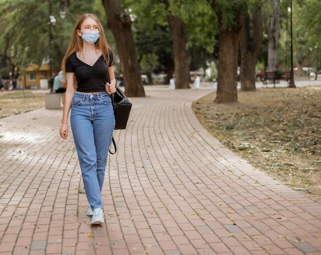 Mulher jovem caminhando usando máscara médica