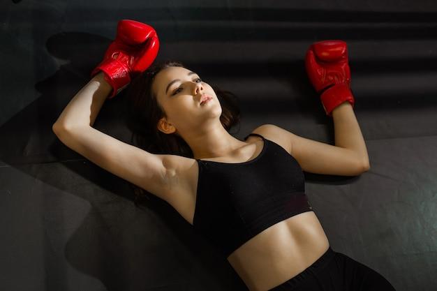 Mulher jovem cansada após treino desportivo com luvas de boxe