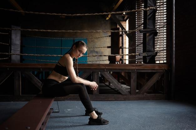Mulher jovem cansada com corpo magro, sentada no banco após um treino de boxe em uma academia moderna, usando roupa esportiva preta e tênis