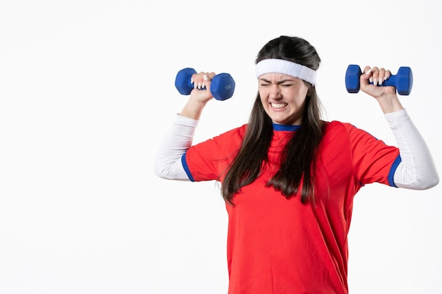 Mulher jovem cansada de frente, com roupas esportivas e halteres azuis