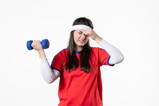 Mulher jovem cansada de frente, com roupas esportivas, malhando com halteres