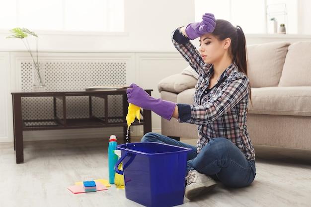 Mulher jovem cansada de limpar a casa na primavera