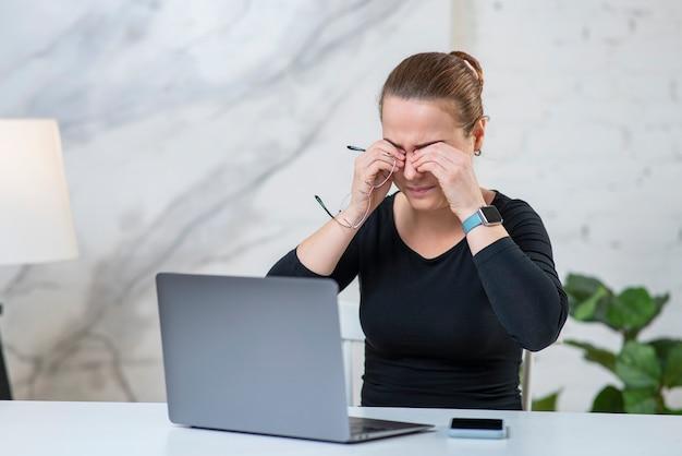 Mulher jovem cansada e cansada segurando óculos, esfregando os olhos, sofrendo de fadiga ocular na frente