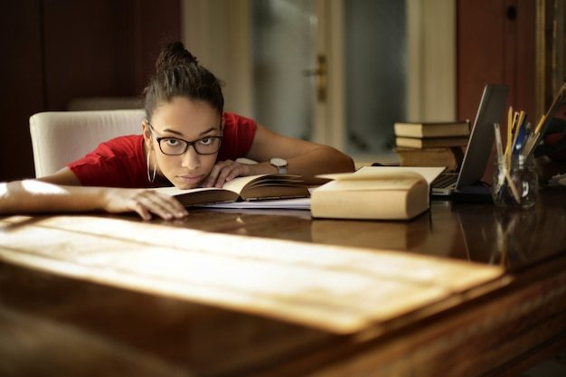 Mulher jovem cansada fazendo lição de casa em casa