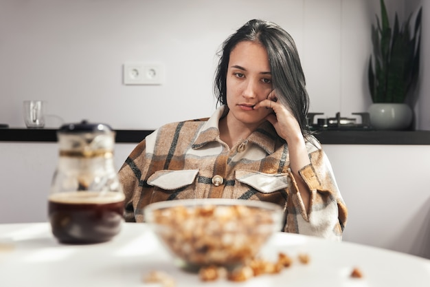 Mulher jovem cansada olha para comida e não quer tomar café da manhã