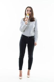Mulher jovem canta em um microfone em um fundo branco