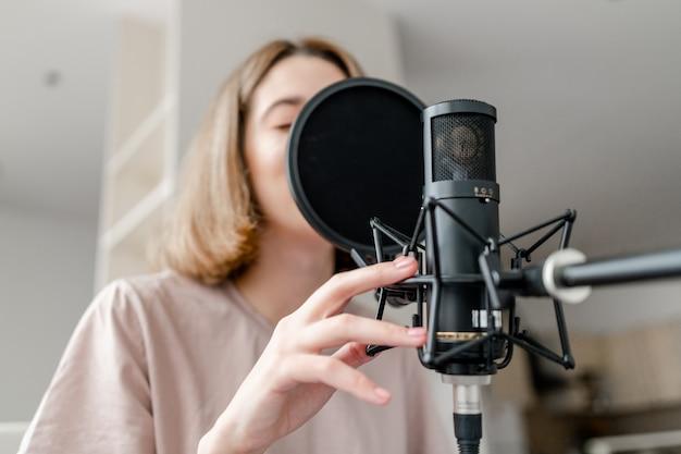 Mulher jovem cantando em close do microfone