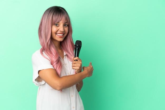 Mulher jovem cantora de raça mista com cabelo rosa isolado em um fundo verde apontando para trás