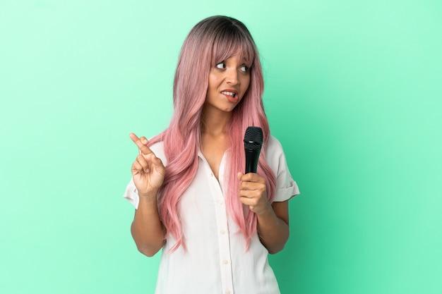 Mulher jovem cantora de raça mista com cabelo rosa isolado em um fundo verde com dedos se cruzando e desejando o melhor