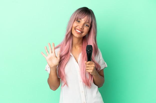 Mulher jovem cantora de raça mista com cabelo rosa isolado em um fundo verde contando cinco com os dedos
