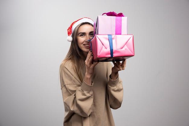 Mulher jovem carregando duas caixas de presentes de natal.