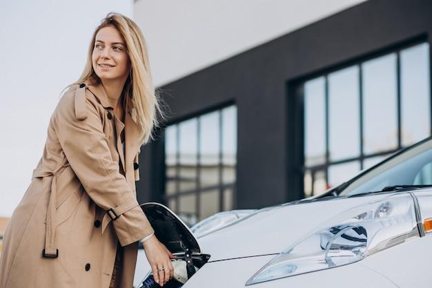 Mulher jovem carregando seu carro elétrico com uma pistola