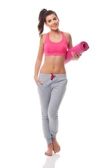 Mulher jovem carregando tapete de ioga