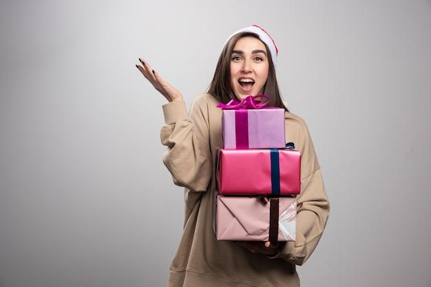 Mulher jovem carregando três caixas de presentes de natal.