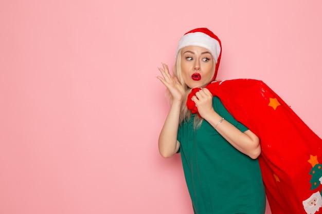 Mulher jovem carregando uma bolsa vermelha com presentes na parede rosa modelo de foto de natal de ano novo em cor de frente