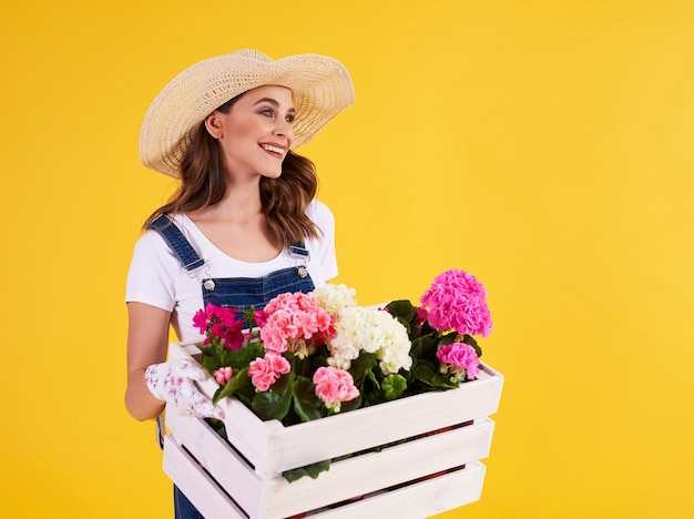 Mulher jovem carregando uma caixa de madeira com lindas flores