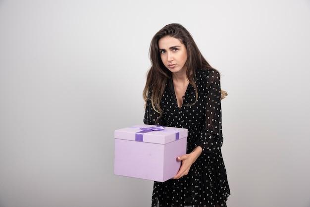Mulher jovem carregando uma caixa de presente roxa
