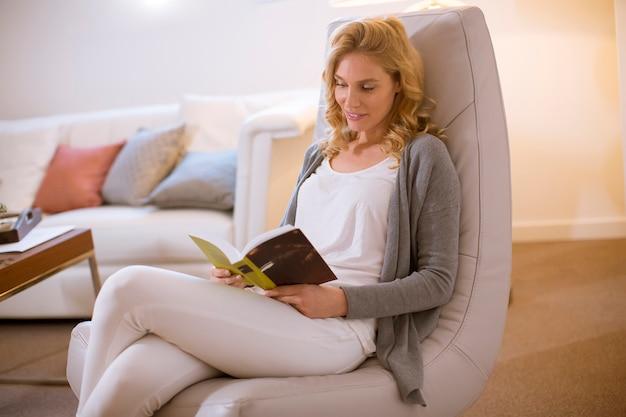 Mulher jovem, casa, sentando, ligado, modernos, cadeira, e, livro leitura