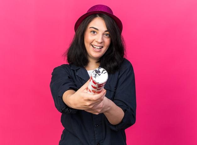 Mulher jovem caucasiana animada com um chapéu de festa apontando para a frente com um canhão de confete olhando para a frente, isolado na parede rosa